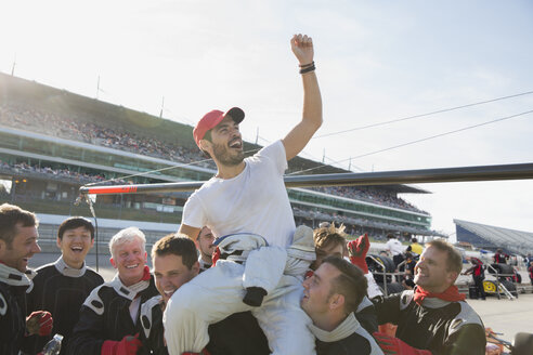 Formula one racing team carrying cheering driver on shoulders, celebrating victory on sports track - CAIF06470