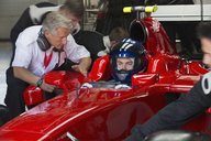 Manager talking to formula one race car driver in repair garage - CAIF06473