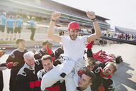 Formula one racing team carrying driver on shoulders, celebrating victory on sports track - CAIF06485