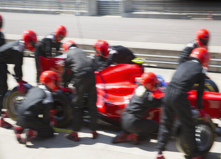 Pit crew replacing tires on formula one race car in pit lane - CAIF06491