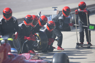 Pit crew with tires ready for nearing formula one race car in pit lane - CAIF06503