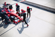 Pit crew replacing tires on formula one race car in pit lane - CAIF06509