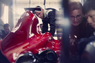Pit crew working on formula one race car in repair garage - CAIF06533