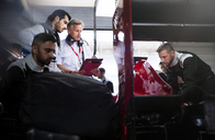 Manager and driver talking behind pit crew working on race car in repair garage - CAIF06542