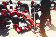Pit crew replacing tires on formula one race car in pit lane - CAIF06545