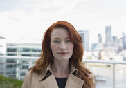 Portrait serious, confident businesswoman with red hair on urban balcony with city view - CAIF06548