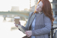 Businesswoman multitasking, drinking coffee and using digital table while talking on cell phone - CAIF06551