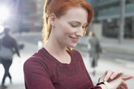 Close up smiling female runner checking smart watch - CAIF06554