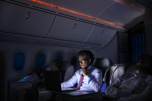 Businessman working at laptop on night airplane - CAIF06566