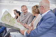 Mature friends looking at map on airplane - CAIF06569