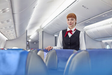 Portrait confident female flight attendant on airplane - CAIF06572