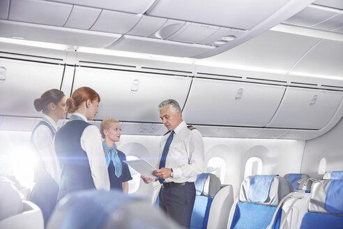 Pilot and flight attendants talking, preparing on airplane - CAIF06575