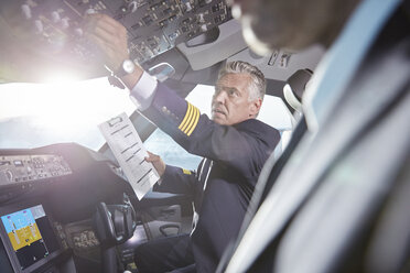 Male pilot with clipboard preparing, adjusting instruments in airplane cockpit - CAIF06578