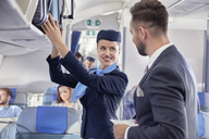 Flight attendant helping businessman with luggage on airplane - CAIF06581