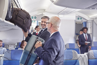 Businessmen loading luggage into storage compartment on airplane - CAIF06584