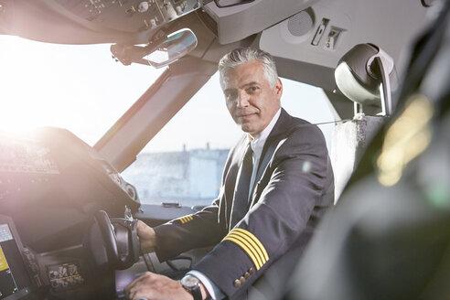 Portrait confident male pilot in airplane cockpit - CAIF06587