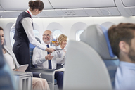 Flight attendant serving whiskey to businessman in first class on airplane - CAIF06596
