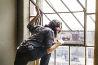 Man looking through window while standing at home - CAVF01152