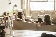Couple talking while sitting in living room at home - CAVF01158
