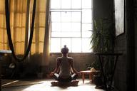Rear view of woman meditating at home - CAVF01161