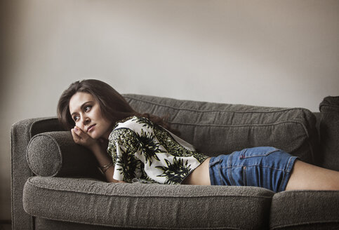 Side view of woman relaxing on sofa at home - CAVF01173