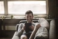 Smiling man using tablet computer while reclining on sofa at home - CAVF01179