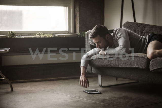 Man looking at tablet computer while lying on sofa - CAVF01182