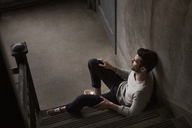 High angle view of man sitting on stairs at home - CAVF01185