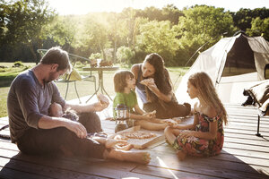 Family eating pizza while sitting on porch - CAVF01206