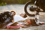 Couple relaxing on gravel road by motorbike - CAVF01221