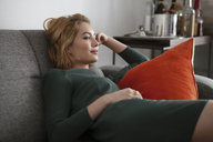 Woman looking away while lying on sofa at home - CAVF01257