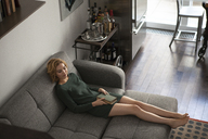 High angle view of woman with book on sofa - CAVF01260