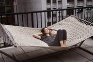 Woman lying on hammock in patio - CAVF01269