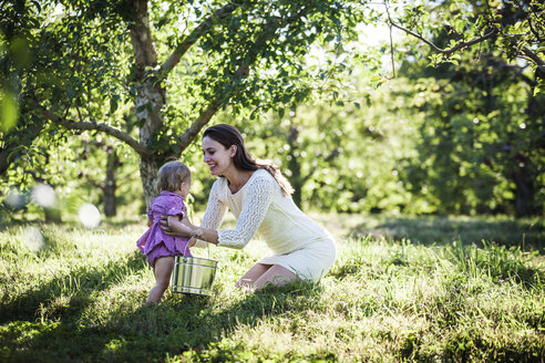 Woman holding daughter with bucket at orchard - CAVF01284