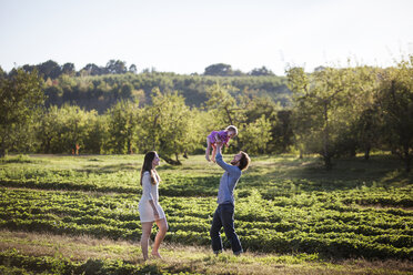 Man lifting daughter while standing with wife on field - CAVF01290