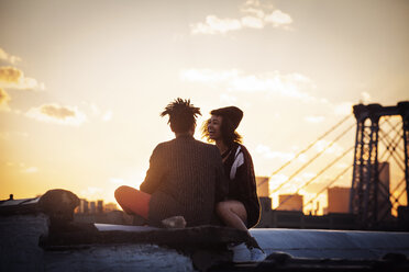 Cheerful couple sitting on retaining wall during sunset - CAVF01320