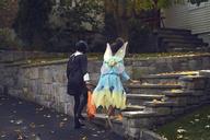 Girls in costume climbing steps against house - CAVF01359