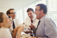 Business people laughing and drinking coffee in office - CAIF06605