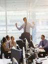 Exuberant businessman celebrating on top of desks in office - CAIF06608