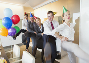 Playful business people with party hats dancing in conga line - CAIF06611