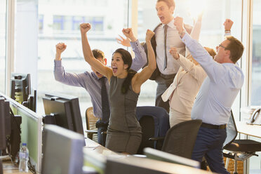 Exuberant business people cheering with arms raised in office - CAIF06614