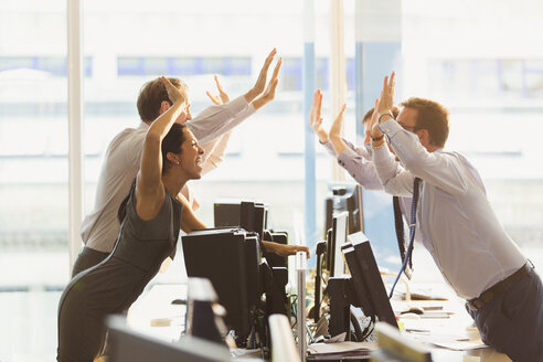 Exuberant business people high-fiving over computers in office - CAIF06617