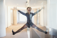 Symmetrical reflection portrait of playful businesswoman with arms and legs apart in office corridor - CAIF06620