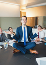 Colleagues watching zen-like businessman meditating in lotus position on conference table - CAIF06626