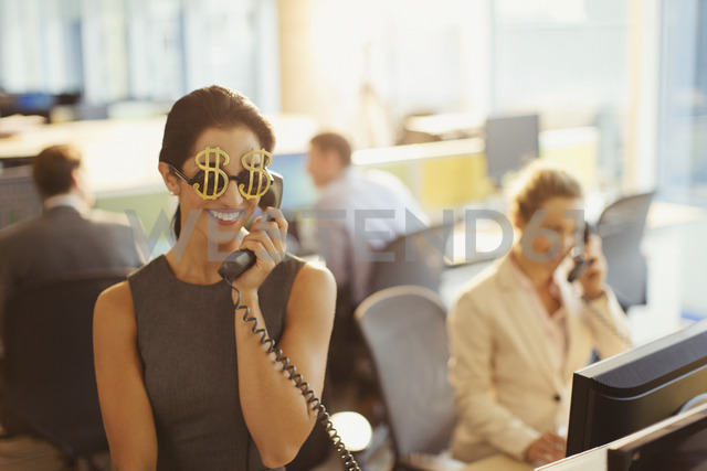 Portrait of smiling businesswoman wearing dollar sign sunglasses answering telephone in office - CAIF06635 - Paul Bradbury/Westend61