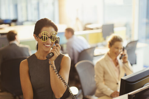 Portrait of smiling businesswoman wearing dollar sign sunglasses answering telephone in office - CAIF06635
