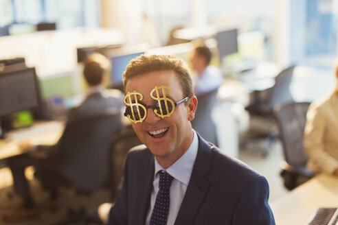 Portrait smiling businessman wearing dollar sign sunglasses in office - CAIF06641