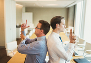 Playful businessmen pretending to duel back to back in conference room - CAIF06647