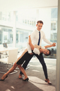Portrait of businessman and businesswoman dancing tango in conference room - CAIF06650