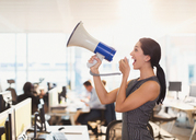 Exuberant businesswoman using megaphone in office - CAIF06653